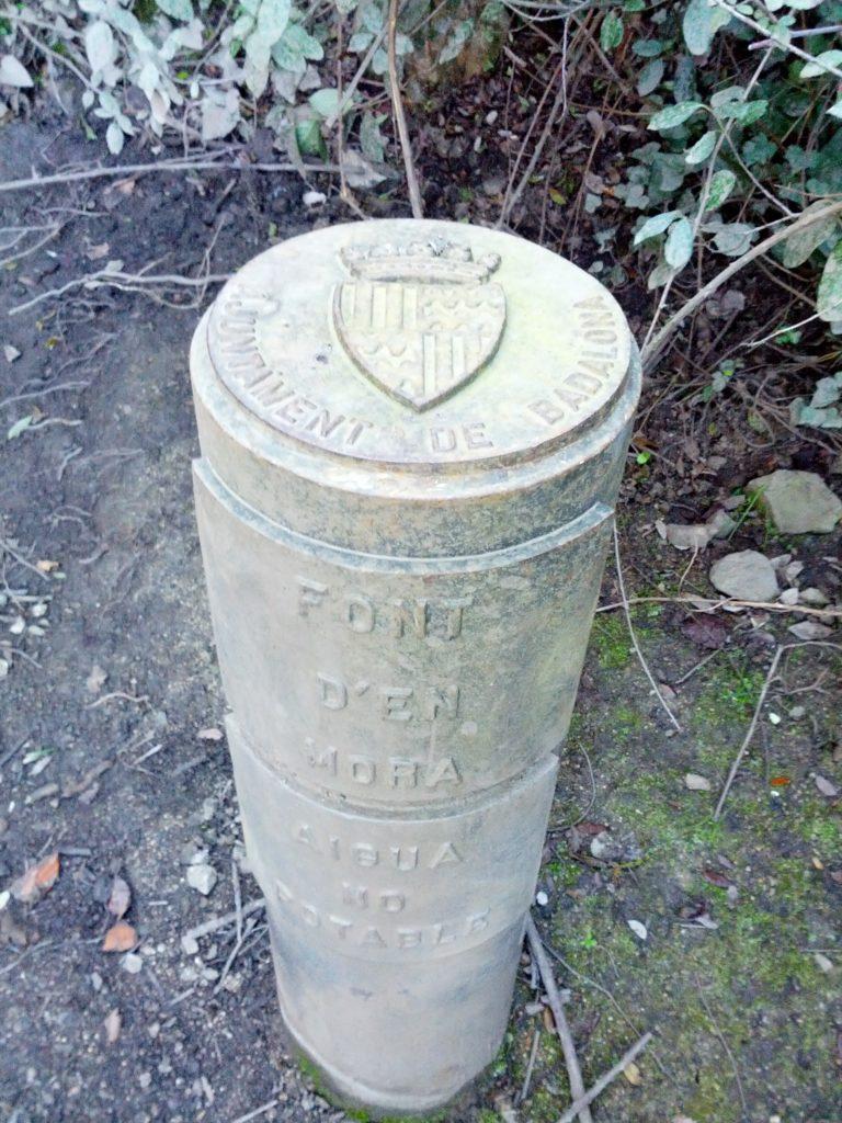 Detall de la pilona amb la inscripció de l'Ajuntament i de la font
