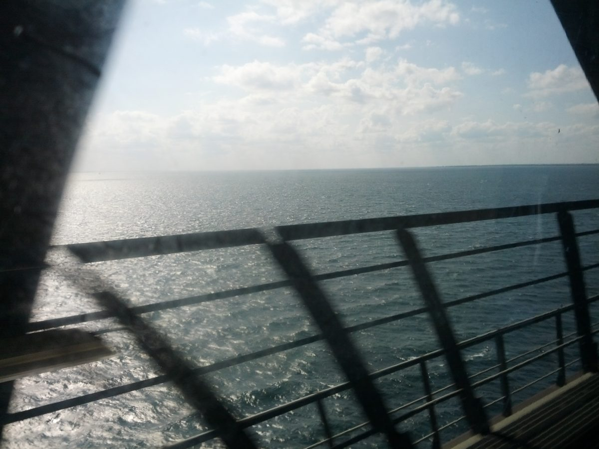 Vista des del tren mentre passa per sobre el mar, la barana queda moguda