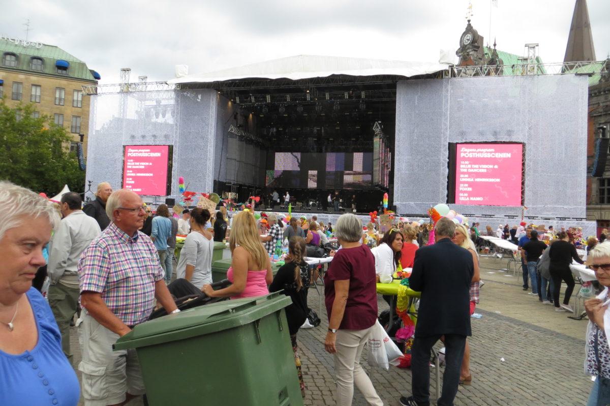 Persones amunt i avall davant l'escenari del concert. Un home arrossega un contenidor de brossa verd.
