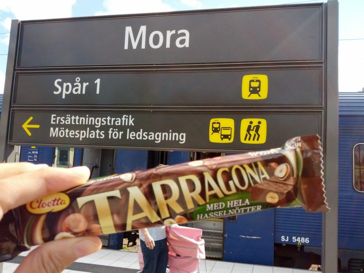 Rètol de l'estació de Mora i en primer terme una xocolatina Tarragona