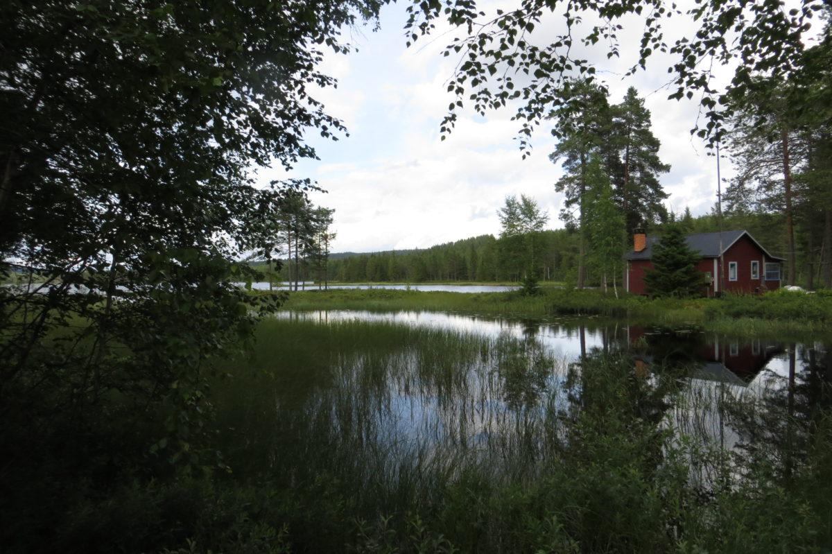 Racó amb un llac i reflexes de l'entorn a l'aigua, amb una casa típica al fonsa la dreta