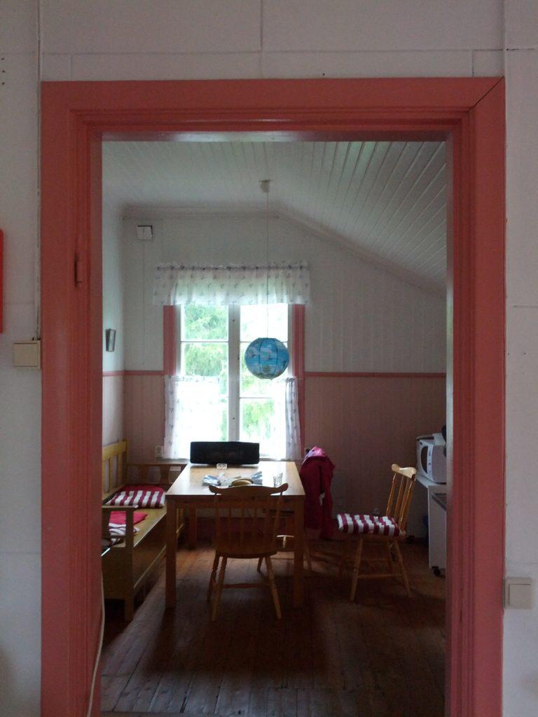 Vista de la cuina amb el marc de la porta rosa