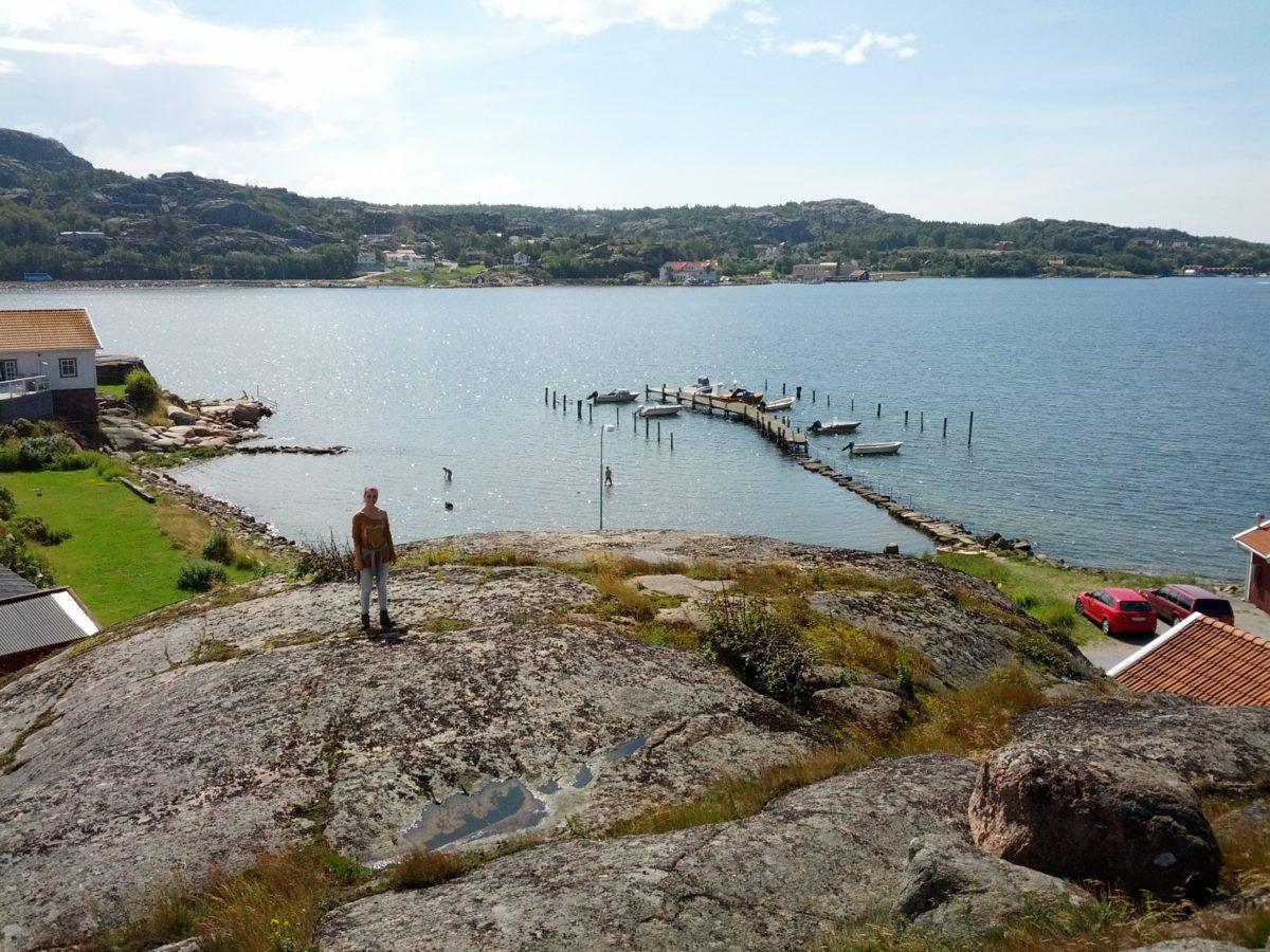 Vista del mar amb un embarcador des de dalt amb una gran roca en primer terme