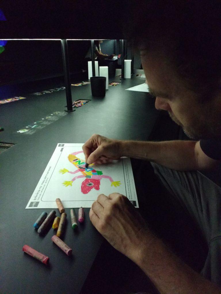 Dani pintant un llargandaix amb ceres en un full de paper