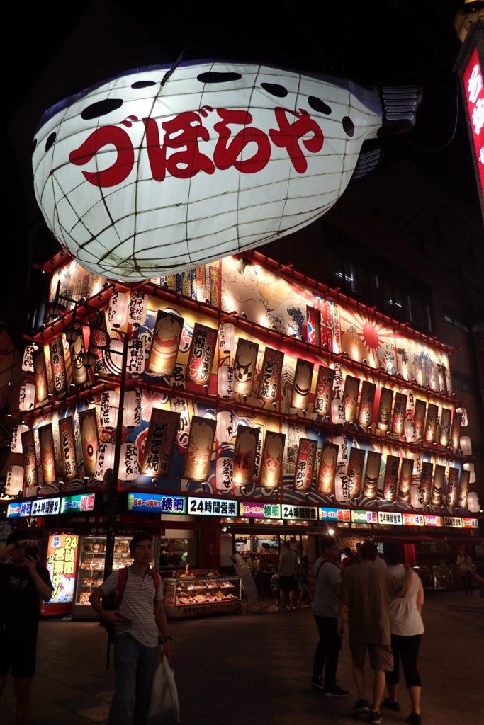 Façana d'un restaurant de Shinsekai il·luminada amb un peix gegant davant