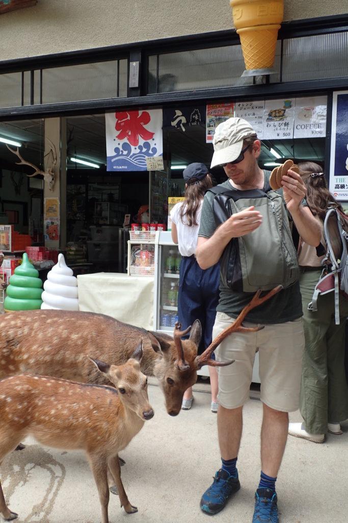 Dani amb dos cérvols que li demanen menjar davant una botiga