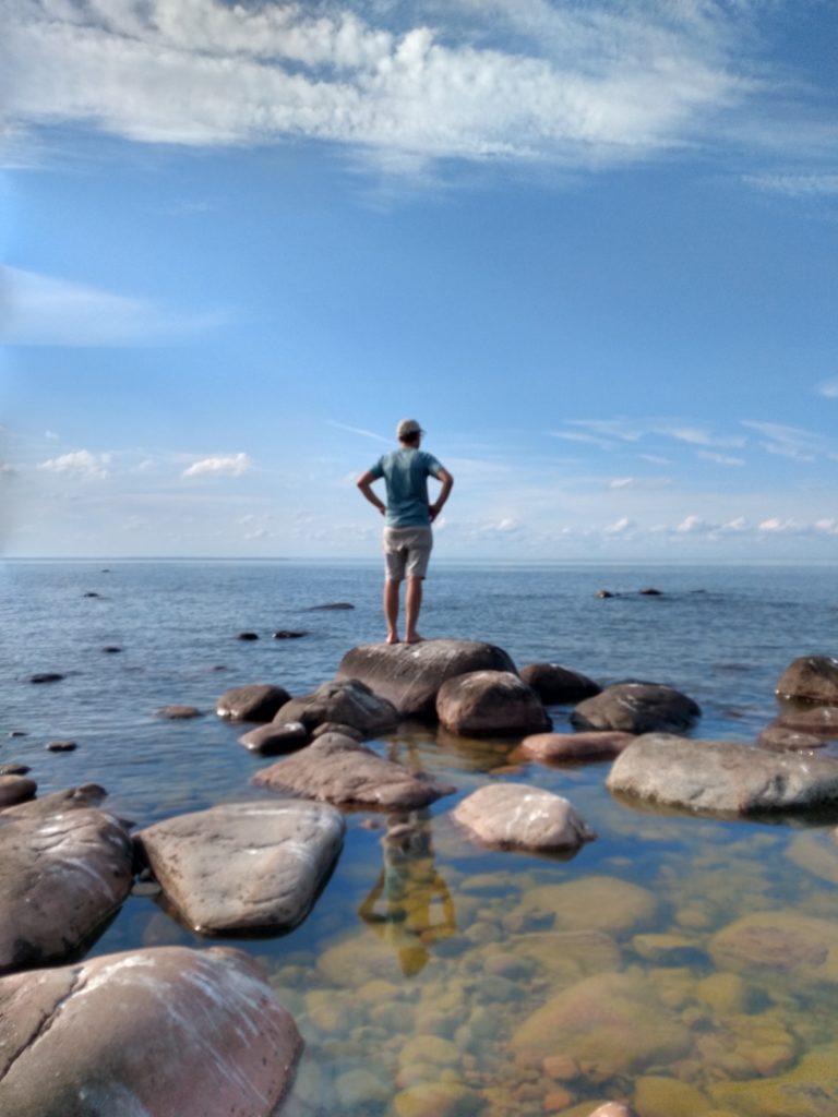 Dani mirant a l'horitzó sobre unes pedres