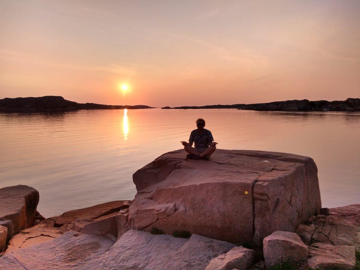 Dani sobre una pedra en postura de meditació amb el sol al fons