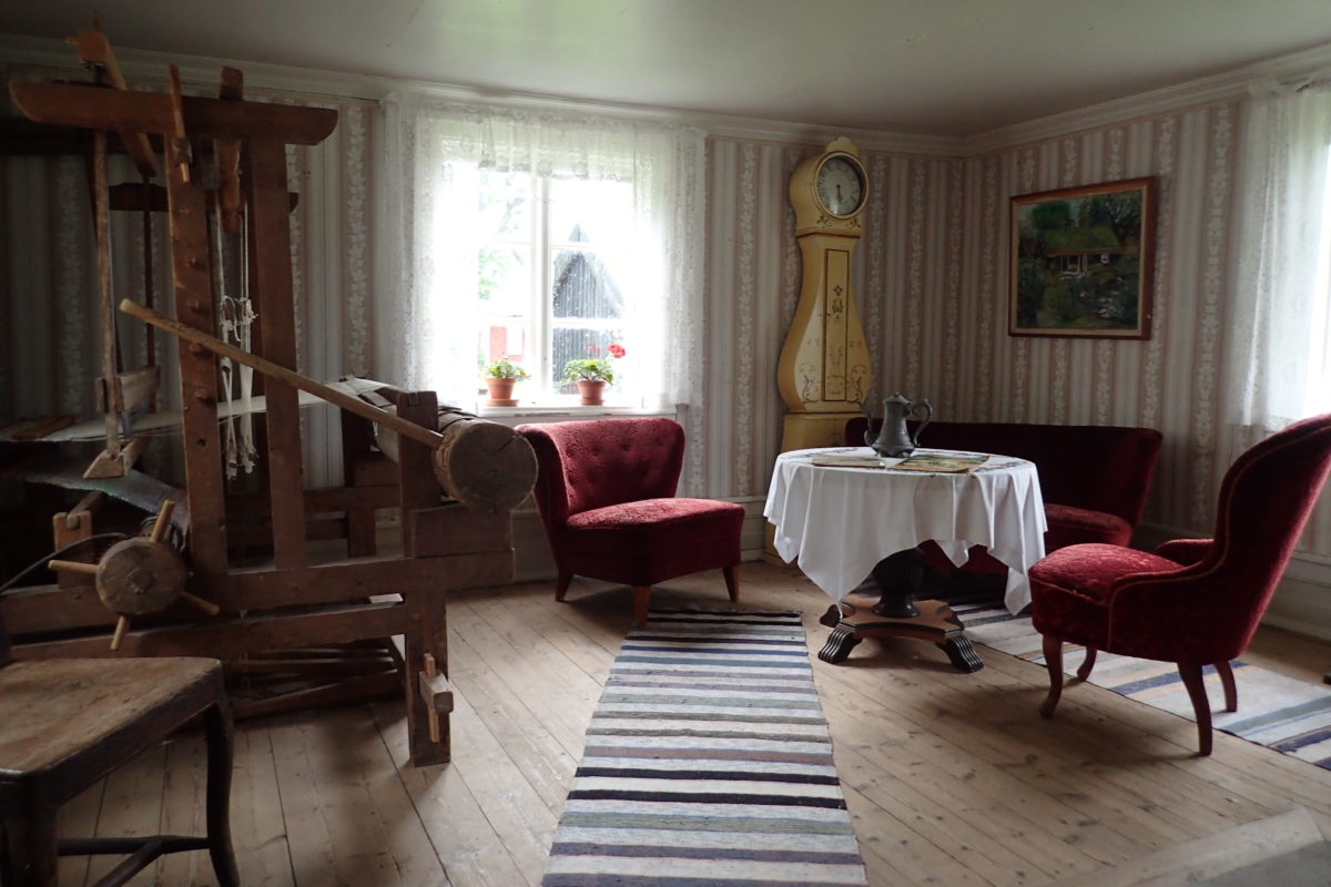 Interior d'una casa amb una butaca i un rellotge de peu