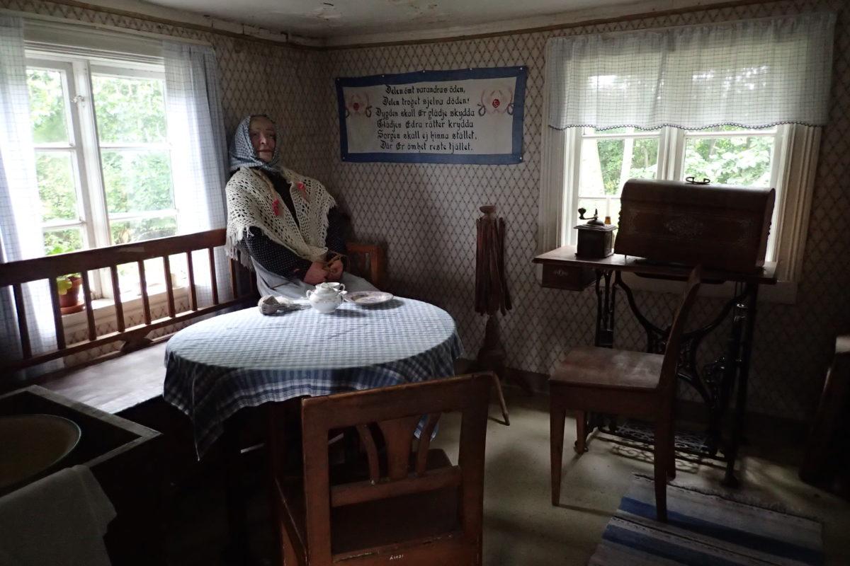 Interior amb una figura d'una dona vella asseguda al fons