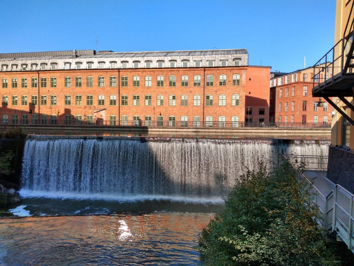 Una cascada amb un edifici al fons
