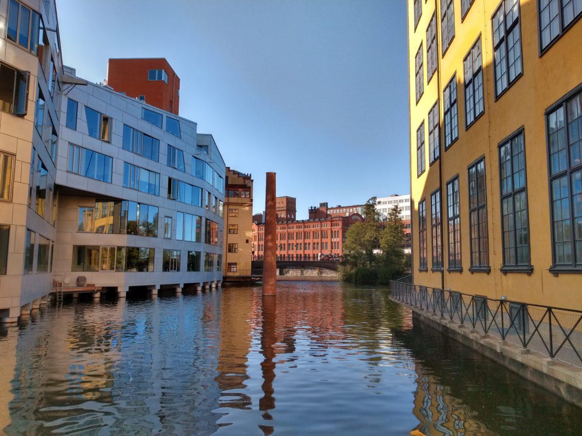 Canal que passa entre dos edificis, talment com un carrer, amb una xemeneia al mig que sobresurt de l'aigua,