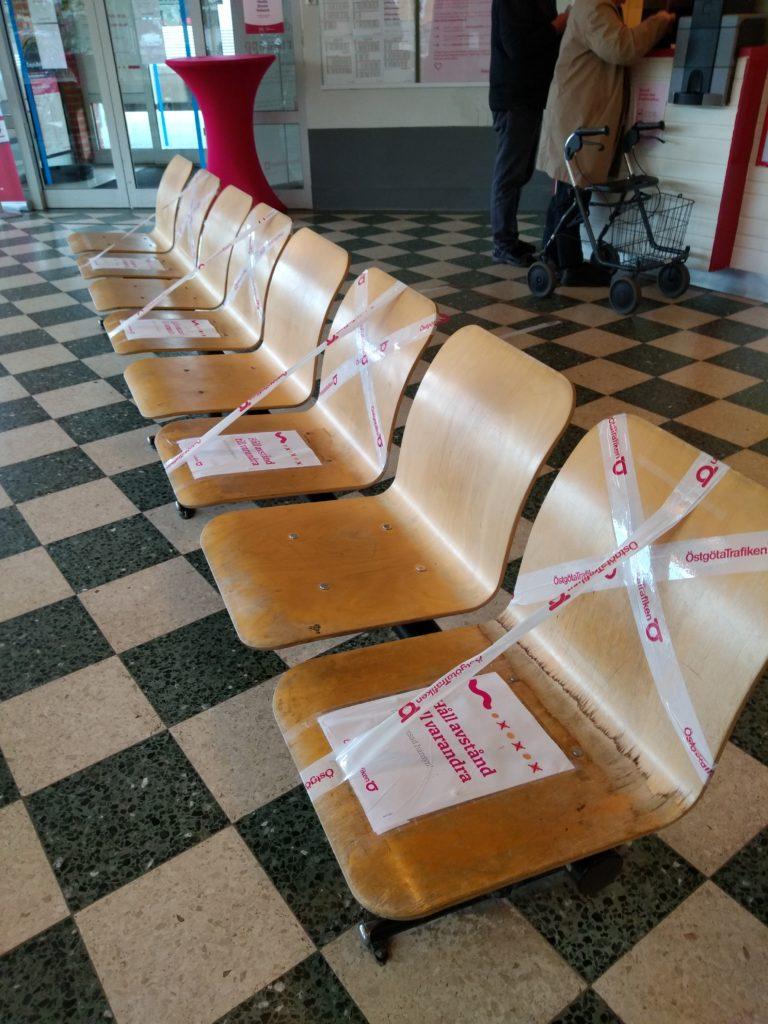Cadires amb cintes que impedeixen seure-hi i amb cartells que demanen mantenir la distància de seguretat.