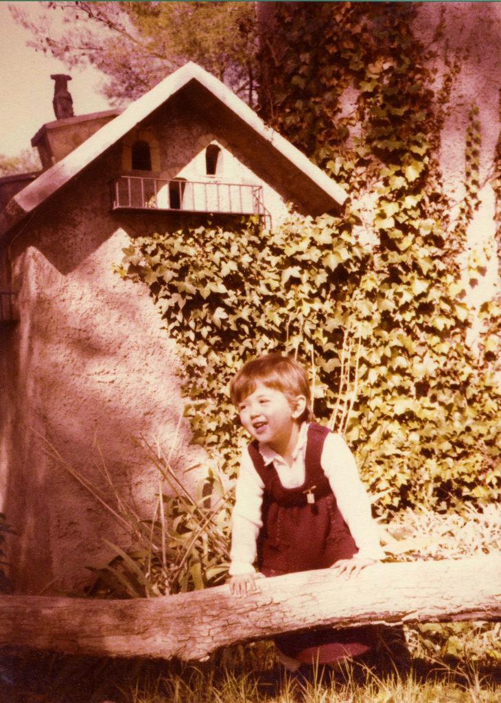 Jo de petita davant una caseta amb teulada a dues aigües